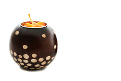 Orange candle in a bown paterned holder Royalty Free Stock Images
