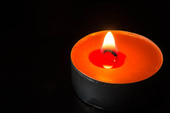 Orange candle burning on a black background Royalty Free Stock Photos