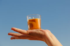 Orange candle in a hand with sky backround Stock Photo