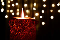 Orange candle over christmas lights Royalty Free Stock Photos