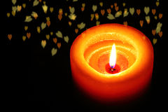 Orange candle with romantic blur hearts. Horizonal Stock Photo