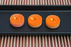 Orange candles in black dish on bamboo. Three orange candles in black dish on bamboo, lighted Royalty Free Stock Image