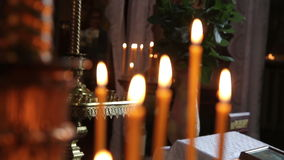 Orange candles burn in the church 1080p Stock Images
