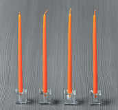 Orange candles on a grey textured background Royalty Free Stock Images