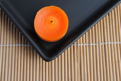 Orange candls in black dish on bamboo background. Orange candle in black dish on bamboo Stock Photo