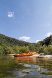 Orange Canoe on River Bank in Nature with Blue Sky Royalty Free Stock Images