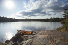 Orange canoe on rocky shore of Boundary Waters lake near sundown Royalty Free Stock Photography