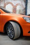 Orange car with alloy wheel indoor Stock Image