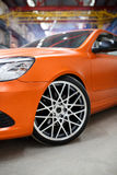 Orange car with alloy wheel indoor Royalty Free Stock Images
