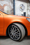 Orange car with alloy wheel indoor Royalty Free Stock Photography