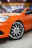 Orange car with alloy wheel indoor. Toned Stock Image