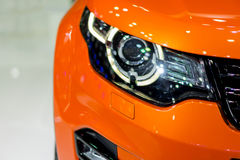 Orange car parked on a white background. Stock Image