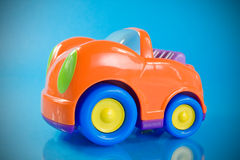 Orange car toy. Over a blue background Stock Photos
