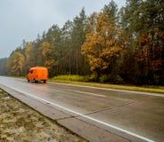 Orange car-van, going along the autumn road at sunset. Stock Photo