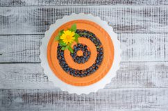 Orange carrot chocolate velour mousse cake with blueberry. An orange chocolate velour cake with flowers, blueberries and basil Royalty Free Stock Image