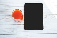 Orange carrot juice and digital device on a white wooden background.  Stock Image