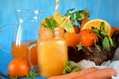 Orange and carrot juice in a glass jar. Decorated with mint, cocktail straw and umbrella on blue background Stock Photo