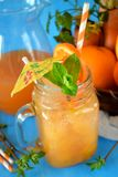 Orange and carrot juice in a glass jar. Decorated with mint, cocktail straw and umbrella on blue background Stock Image