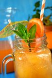 Orange and carrot juice in a glass jar. Decorated with mint, cocktail straw and umbrella on blue background Stock Photos