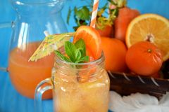 Orange and carrot juice in jugs. Decorated with mint, cocktail straw and umbrella on blue background Royalty Free Stock Photography