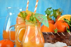 Orange and carrot juice in jugs. Decorated with mint, cocktail straw and umbrella on blue background Stock Image