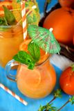Orange and carrot juice in jugs. Decorated with mint, cocktail straw and umbrella on blue background Stock Photos