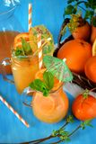 Orange and carrot juice in jugs. Decorated with mint, cocktail straw and umbrella on blue background Stock Photography