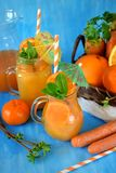 Orange and carrot juice in jugs. Decorated with mint, cocktail straw and umbrella on blue background Stock Images