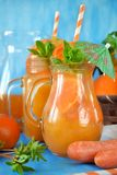 Orange and carrot juice in jugs. Decorated with mint, cocktail straw and umbrella on blue background Stock Photo