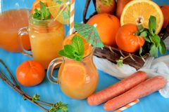 Orange and carrot juice in jugs. Decorated with mint, cocktail straw and umbrella on blue background Royalty Free Stock Image
