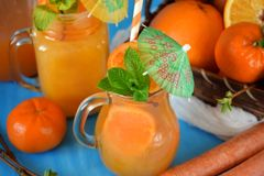 Orange and carrot juice in jugs. Decorated with mint, cocktail straw and umbrella on blue background Royalty Free Stock Images