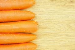 Orange carrot side of wood background Stock Photography
