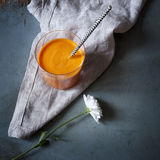 Orange carrot smoothie on glass on rustic table with flower and napkin Royalty Free Stock Photo