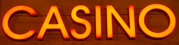 Orange casino neon sign. Casino neon sign on the wall - panoramic composition Royalty Free Stock Photos