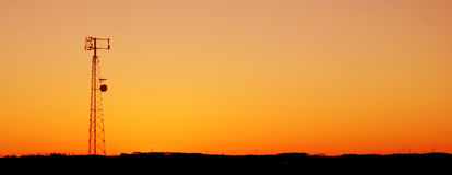 Orange Cell Tower Silhouette. A cell phone tower silhouette in the sunset Stock Photos