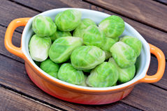 Orange ceramic bowl with brussels sprouts. On table Royalty Free Stock Photography