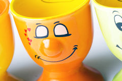 Orange ceramic egg holder. Cute orange ceramic egg holder with a smiley face royalty free stock image