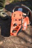Orange chain saw in the garden Stock Photo