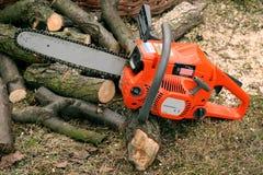 Orange chainsaw. And wood stock image
