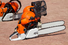 Orange chainsaw. And helmets on the ground Stock Images