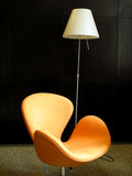 Orange chair. A orange chair next to a lamp stock image