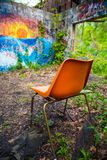 Orange chair in abandoned building. Ruins with graffiti and overgrowth stock images