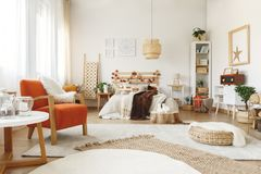 Orange chair in bedroom. Big comfy orange chair in a bright spacious bedroom royalty free stock images