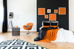 Orange chair in retro bedroom. Sunglasses and glass bottle on metal designed table near orange chair in retro bedroom stock photos