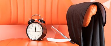 On an orange chair is a set of shaving items and a black alarm clock royalty free stock images