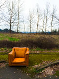 Orange Chair Urban Decay. Urban decay and an abandoned orange chair next to some winter trees Stock Photo