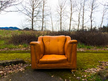 Orange Chair Urban Decay. Urban decay and an abandoned orange chair next to some winter trees stock images
