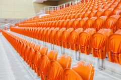 Orange chairs stand in a row in a covered stadium. Stock Image