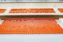 Orange chairs stand in a row in a covered stadium. Royalty Free Stock Images