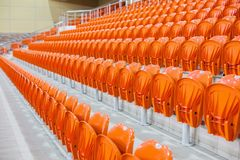 Orange chairs stand in a row in a covered stadium. Stock Photos